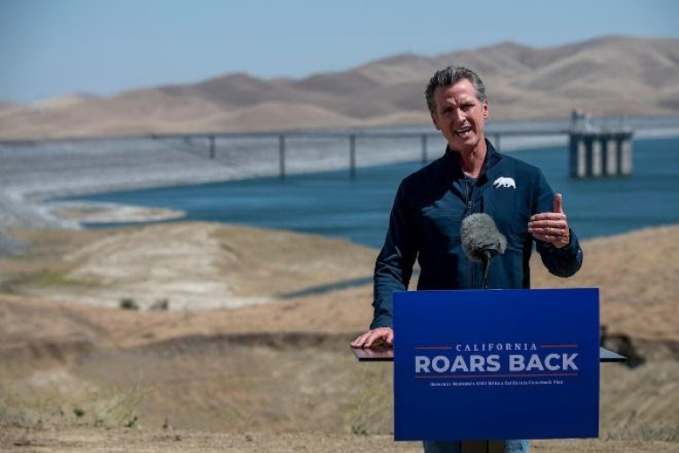 California Governor Gavin Newsom speaks in front of a reservoir experiencing low water levels behind a podium reading CALIFORNIA ROARS BACK.
