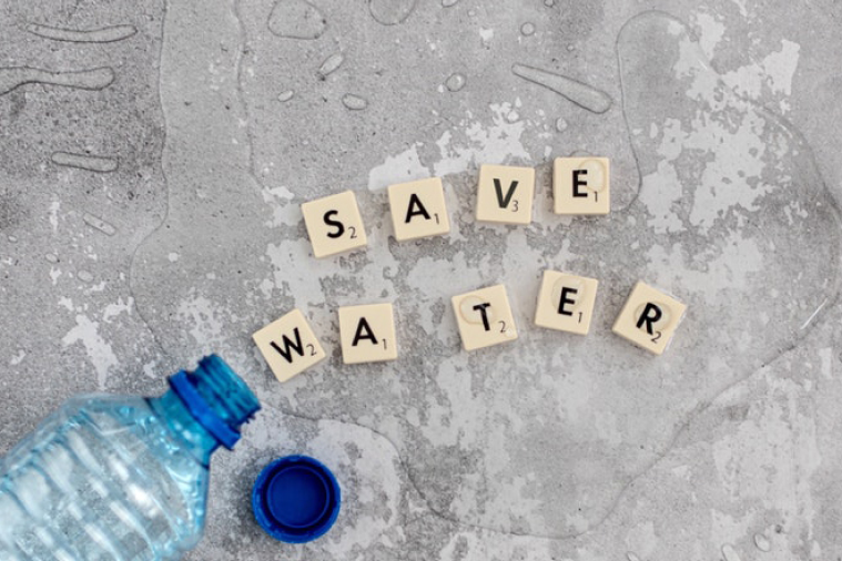 Spilled water on concrete with letter tiles that spell out SAVE WATER